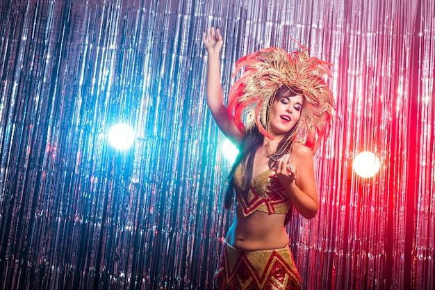 골드 의상을 입고 아름다운 여성 삼바 댄서