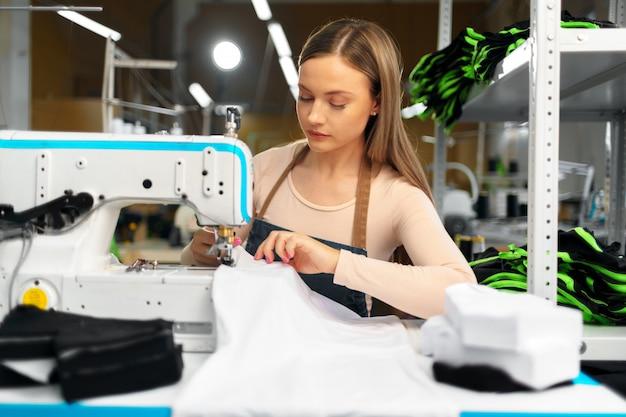 Красивая женская швея работает с тканью на своем рабочем месте