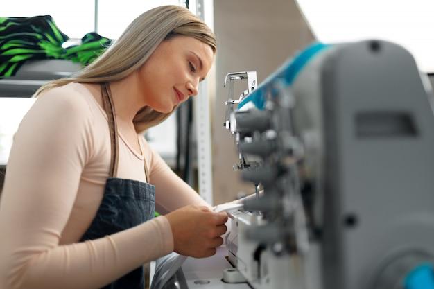Красивая женская швея работая с тканью на ее рабочем месте