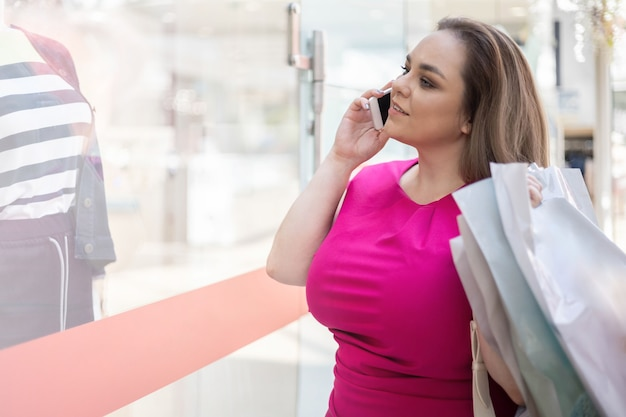 紙の買い物袋を保持しているファッションブティックのショーケースを見ている美しい女性買い物中毒者
