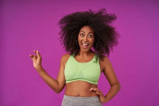 Красивая женщина, демонстрирующая свои приятные эмоции на фиолетовом, в светло-зеленом спортивном топе, радостно улыбается с широко открытым ртом, держа одну ладонь на талии и поднимая другую вверх