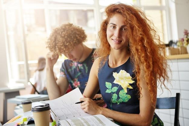 彼女のコピーブックで演習を行うコーヒーショップで座っている美しい女性