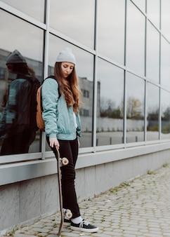Bello pattinatore femminile che tiene il suo skateboard