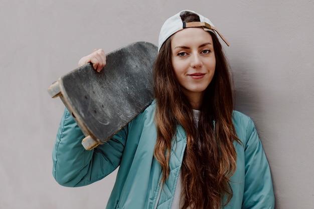 Красивая фигуристка держит ее скейтборд