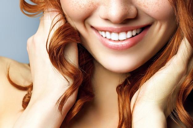 歯のホワイトニング処置後の美しい女性の笑顔。歯の手入れ。歯科の概念