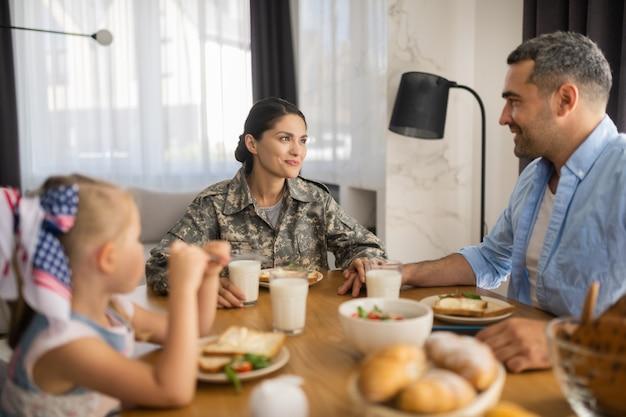 Красивая женщина-солдат. красивая женщина-солдат проводит утро с мужем и дочерью