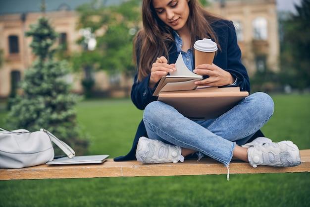 혼자 벤치에 책과 커피 한잔과 함께 봄 날씨를 즐기는 아름다운 여성 학생