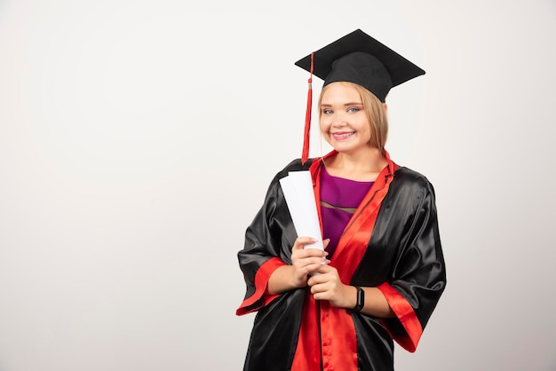 Beautiful female student in gown holding diploma. high quality photo