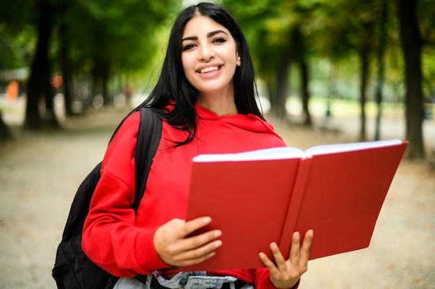 屋外の本を持っている美しい女子学生