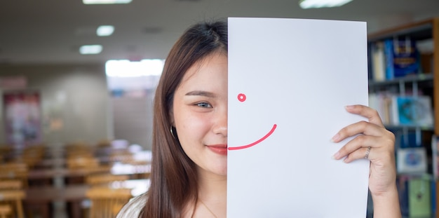 Beautiful female student holds a paper drawing a smile with red ink