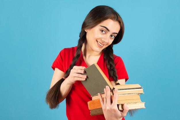 Красивая студентка в красной футболке, внимательно читая книгу на синей стене.