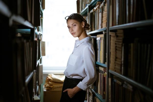 Красивая студентка в рубашке стоит между рядами в библиотеке, на книжных полках стоит книг. темное фото