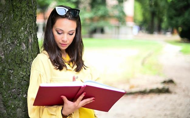 屋外で本を読んでいる美しい女子学生