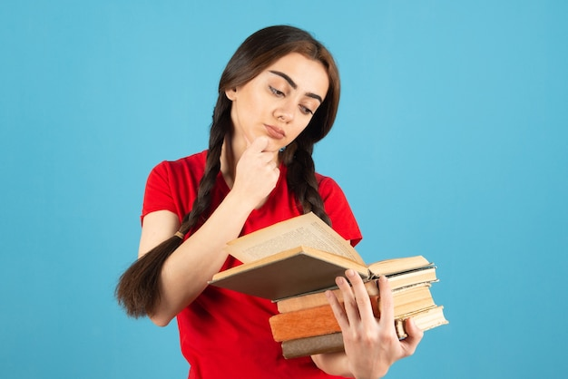 Beautiful female student in red t-shirt attentively reading book on blue wall.