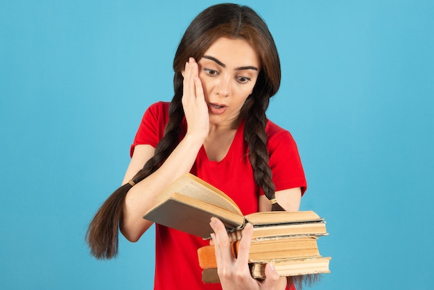 Beautiful female student in red t-shirt reading book with shocked expression.