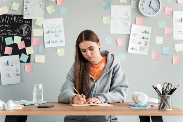 Красивая студентка учится за столом на фоне серой стены.