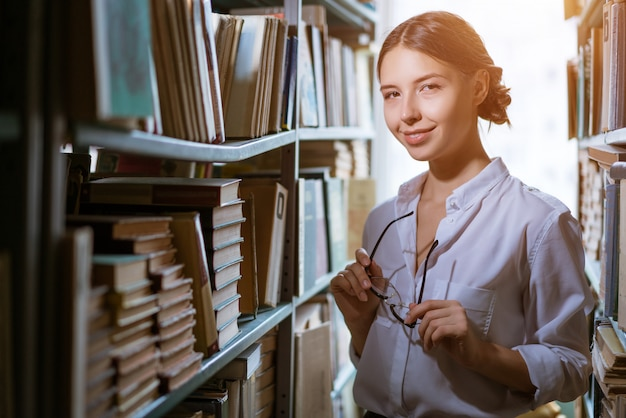 Beautiful female student in a white shirt stands between the rows in the library, bookshelves worth of books. dark photo