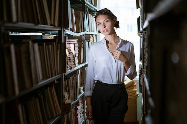 Beautiful female student in a white shirt stands between the rows in the library