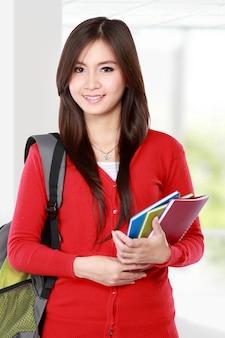 Красивая студентка с книгами улыбается