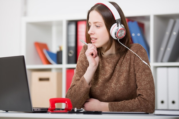 Beautiful female student with headphones listening to music and learning. hold the handle in his hand and looking at laptop monitor