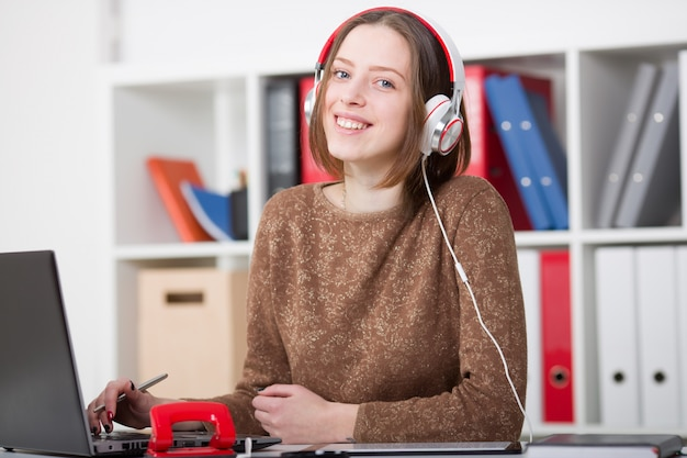 Beautiful female student with headphones listening to music and learning