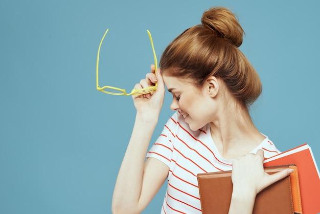 青い教育科学研究所でメモ帳と黄色い眼鏡をかけた美しい女子学生。