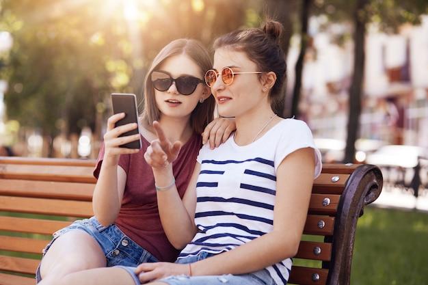 트렌디 한 그늘에서 아름다운 여성 청소년, 스마트 폰에서주의 깊게 보이고, 온라인 쇼핑을하고, 새로운 여름 복장을 선택하고, 공원에서 벤치에 포즈를 취하고, 햇볕이 잘 드는 따뜻한 날씨를 즐기십시오. 레크리에이션 개념