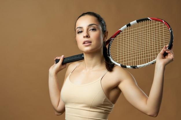 Красивая теннисистка держит ракетку на плечах и смотрит в камеру. изолированные на бежевом фоне