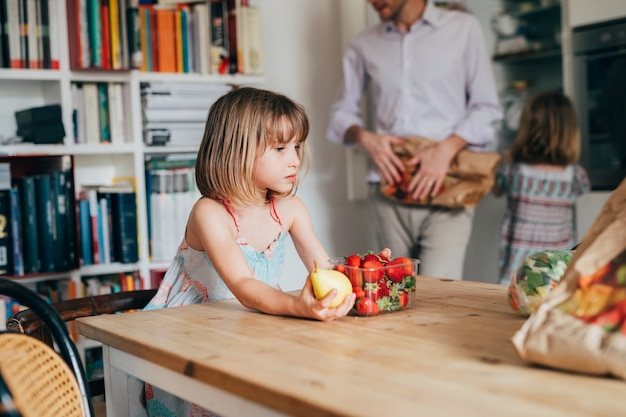 Beautiful female toddler indoor at home kitchen holding fruits