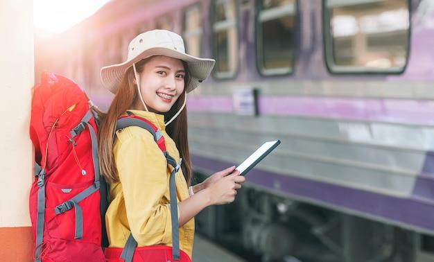 Красивая женщина-путешественница с рюкзаком с помощью планшета ищет места назначения, стоя на вокзале, улыбаясь и глядя вперед