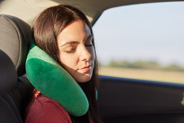 Beautiful female uses neck pillow for sleeping in car, has trip on long distance, tries to relax, feels pain in neck for being in one position much time. people, travelling, comfort, journey concept