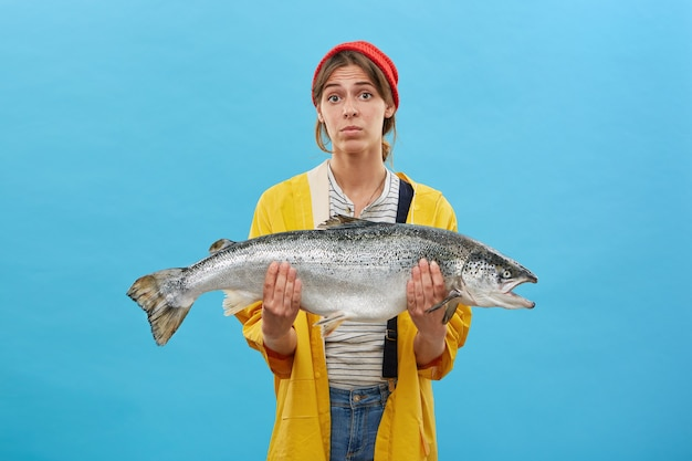 Beautiful female wearing red hat, yellow raincoat and holding huge fish in hands