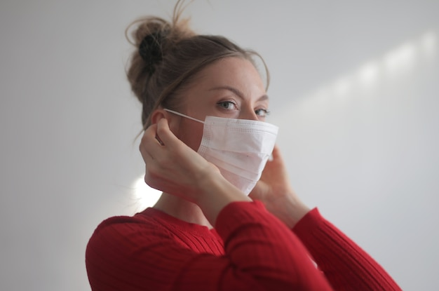 Beautiful female wearing a red shirt and a surgical mask on white