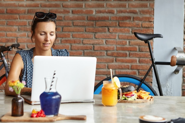 モダンなコーヒーショップで無料のwi-fiを使用して、彼女の頭にサングラスをかけ、インターネットを閲覧し、ソーシャルネットワーク経由でニュースフィードを確認し、オンラインでメッセージを送信している美しい女性