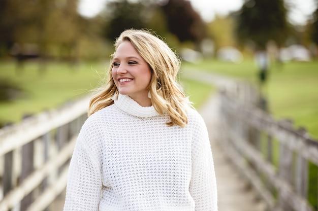 Bella femmina che indossa un maglione bianco e sorridente