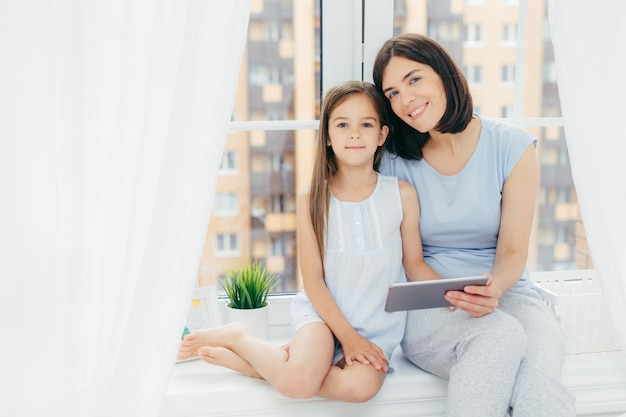 Beautiful female with dark hair, dressed in casual clothes, holds digital tablet, sits near her daughter, watch something