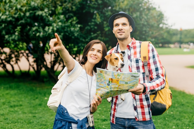 Beautiful female with dark hair showing way to man who lost in city. handsome guy with dog having journey in park, holding map in hands asking passerby how to reach fountain. vacations and travelling