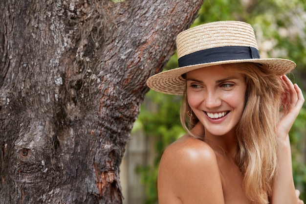 Beautiful female with naked body, looks away while poses near big tree outdoor, wears stylish summer hat, enjoys good recreation in tropics, has pleasant charming smile. people, beauty concept