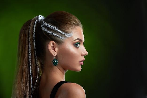 뷰티 살롱, 완벽한 청동 피부, 긴 속눈썹, 녹색 색상의 메이크업 후 세련된 헤어 스타일을 가진 아름다운 여성.