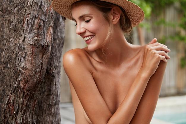 日焼けした健康的な純粋な肌を持つ美しい女性は、トロピカルビューに対してヌードをポーズし、目をそらし、前向きな笑顔を持ち、写真を撮られることをうれしく思い、完璧な体型をしています。美容とスキンケア