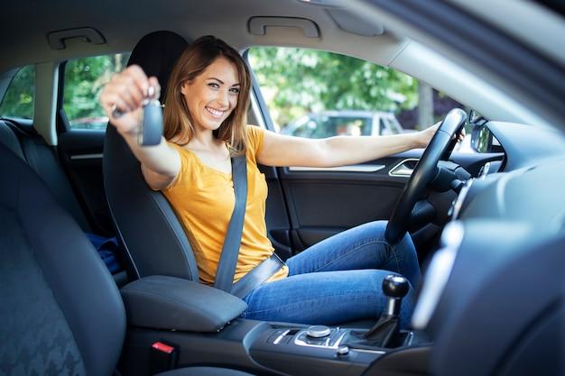 아름다운 여성 여성 드라이버가 그녀의 차량에 앉아 드라이브 준비가 차 열쇠를 들고