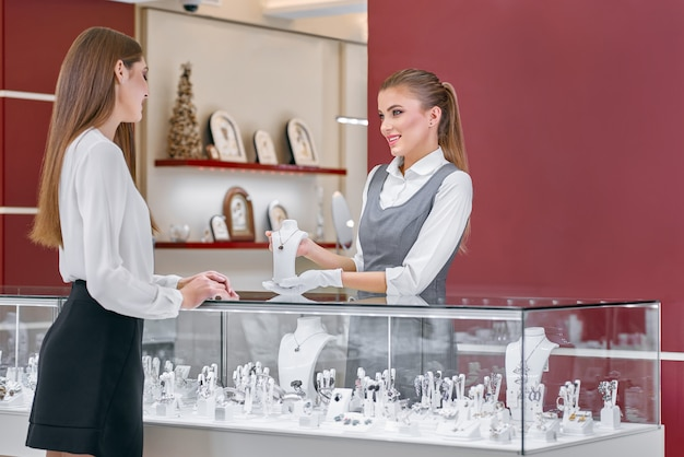 Beautiful female worker of a jewelry store showing a necklace to a woman near the counter