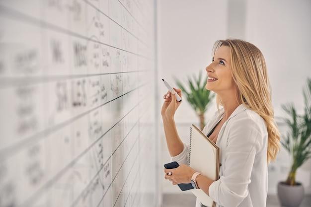 Красивая женщина-работник смотрит на информацию на доске планировщика и улыбается, держа маркер, альбом для рисования и смартфон