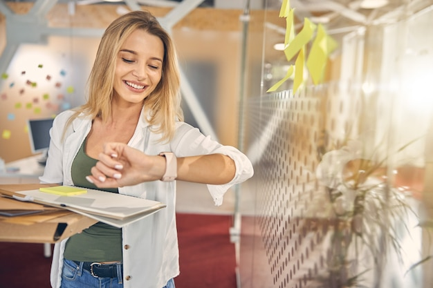 Beautiful female worker looking at her watch and smiling while holding papers