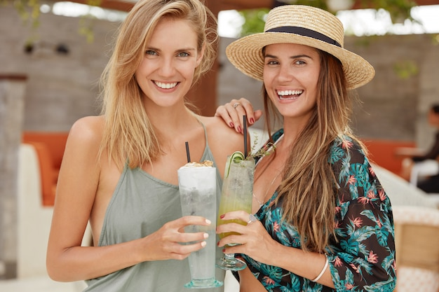 Beautiful females stand close to each other, have positive looks, recreate at beach resort, hold fresh tasty cocktails, embrace. homosexual female couple like spend free time at bar in hotel.