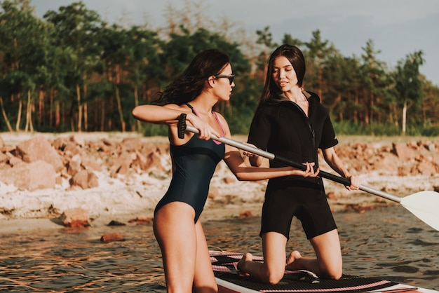 Beautiful females in wetsuit rowing surf with paddle.