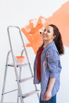 ペイントローラーで壁を塗る美しい女性。若い美しい女性の絵画の肖像画