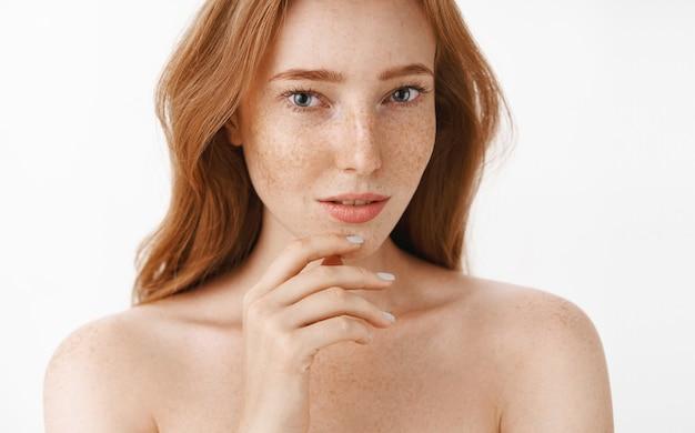 손가락으로 부드럽게 턱을 만지고 아름다움과 피부를 돌보는 감각적이고 편안한 응시와 얼굴과 몸에 자연스러운 붉은 머리카락과 주근깨가있는 아름다운 여성스럽고 매력적인 여성
