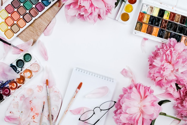 Beautiful feminine flatlay mockup with notebook, stationery supplies, watercolors and pink peonies on white
