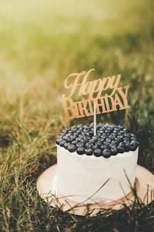 Красивый праздничный творожный детский торт с черникой с надписью happy birthday. вертикальный. на заднем плане солнечный луч и зеленая трава. место для текста. поздравления с днем рождения